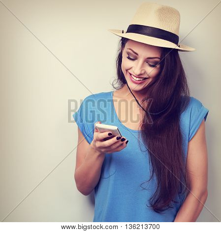 Happy Natural Emotion Woman In Summer Hat Texting The Sms On Mobile Phone. Vintage Toned Portrait
