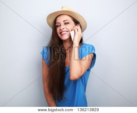 Beautiful Laughing Woman In Summer Hat Talking On Mobile Phone On Blue Background