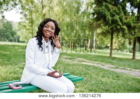 Close Up Portrait Of Stylish And Beautiful Black African American Girl Sitting On Bench With Mobile
