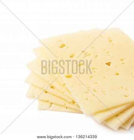 Twisted pile of cheese slices isolated over the white background, close-up crop fragment