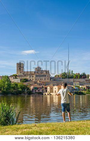 Zamora, Spain - June 19 2016: Fisherman fishing in Duero river with acenas (water mills) and San Salvador Cathedral of Zamora in background. Castilla y Leon Spain.