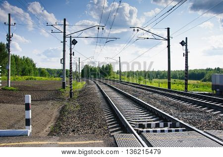 Rail crossing in the countryside in summer cloudy day