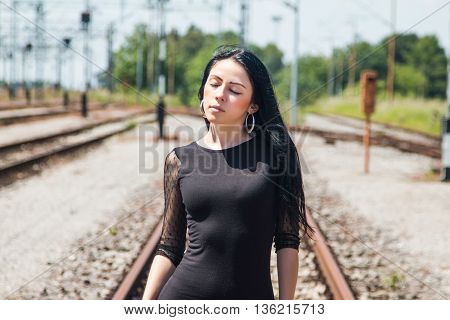 Half length of a young pretty girl in black dress and nylons walking down rail tracks, cargo wagons in background, eyes closed