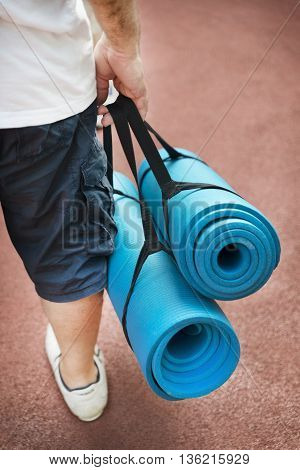 Man Holding Sports Mat For Outdoor Exercise