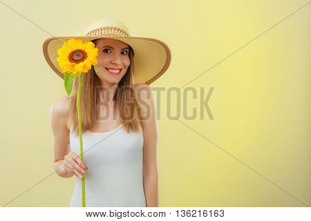 Closeup portrait of attractive summer woman in straw hat with sunflower in hand on yellow background