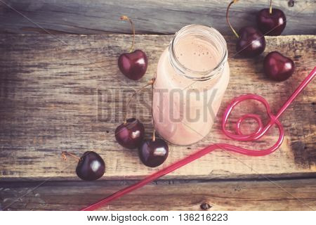 Cherry milkshake on vintage background. Top view with copy space, tinted