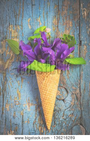 Bouquet of blue clematis in ice cream waffle cone on vintage background. Gardening concept