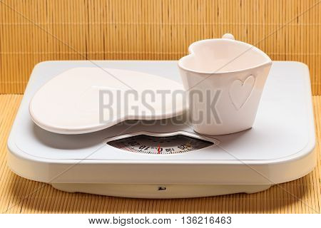Empty heart shaped plate saucer and mug cup on weighing scale. Weight loss concept.