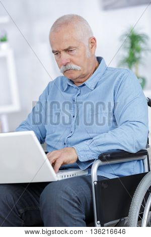disabled senior man sitting in wheelchair using laptop