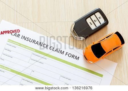 Top view of Approved car insurance claim form with car key and car toy on wooden desk concept