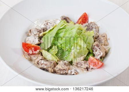 salad with meat in a creamy sauce ase lettuce romaine iceberg cherry tomatoes