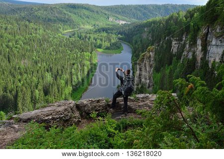 man standing at the top of mountain makes photo with smartphone.