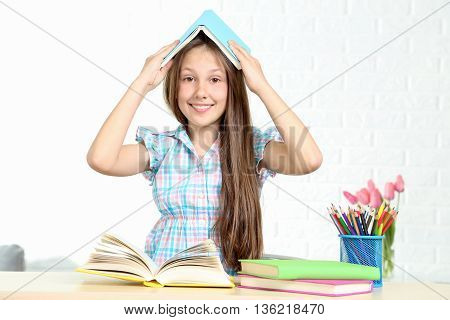 Young girl sitting at the desk and reading book