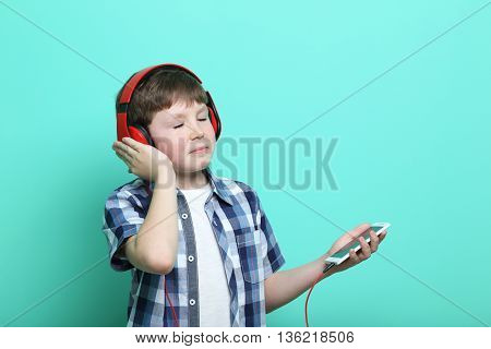 Portrait Of Young Boy With Headphones And Smartphone On Mint Background
