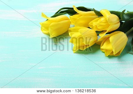 Bouquet Of Yellow Tulips On A Mint Wooden Table
