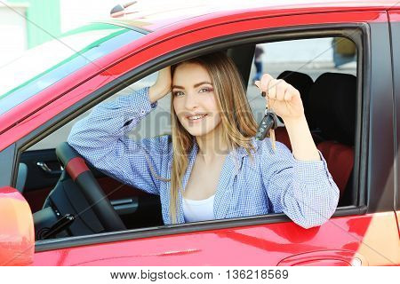 Beautiful Young Girl Sitting In Red Car And Showing The Car Key