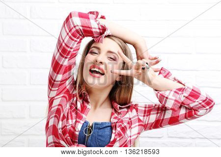 Portrait Of A Beautiful Hipster Girl On Brick Wall Background