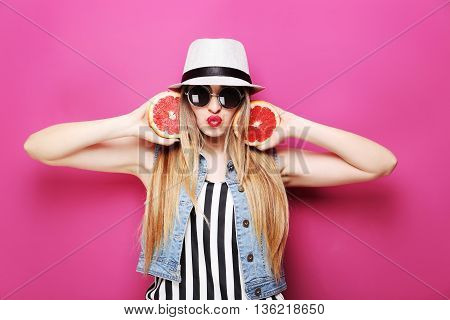 Portrait Of A Beautiful Hipster Girl With Grapefruit On Pink Background