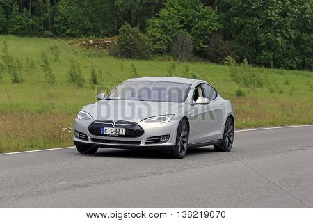 PAIMIO, FINLAND - JUNE 23, 2016: Grey Tesla Model S electric car moves along asphalt road in South of Finland at summer.