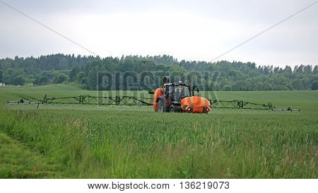 SALO, FINLAND - JUNE 25, 2016: Farmer sprays wheat field with Valtra tractor and Amazone 1501 UF mounted sprayer in June in South of Finland. The boom width is 24 meters.