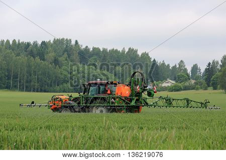 SALO, FINLAND - JUNE 25, 2016: Farmer sprays wheat field with Valtra tractor and Amazone 1501 UF mounted sprayer in June in South of Finland.