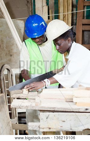 next to her teacher and assistant her , the young student saw the wood with the saw.