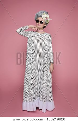 Little beautiful princess in dot dress on soft pink background. Flowers are on head. White-grey hair and sunglasses.