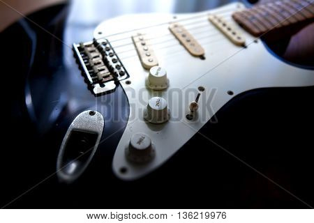 Instrument of creation. A black electric guitar in light and shadow. Focus on