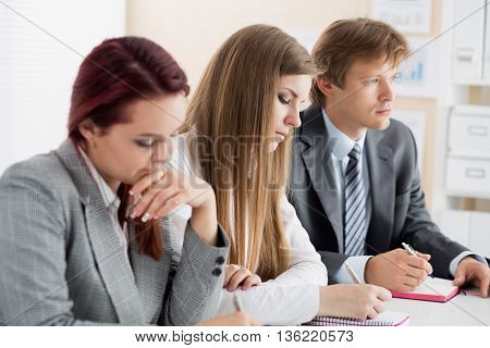 Students or businesspeople hands writing something during conference. Business meeting blogging or professional education concept