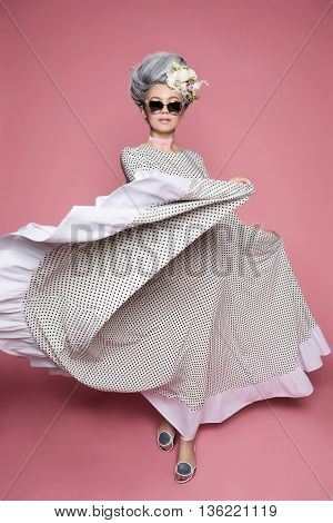 Dynamic photo of little beautiful princess in dot dress on soft pink background. Flowers are on head. White-grey hair and sunglasses.