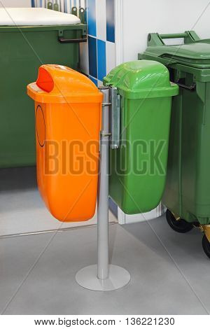 Green and Orange Plastic Public Trash Cans at Pole