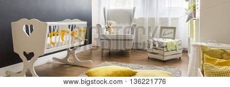 Stylish newborn's room illuminated through a large window with white furniture and a fluffy carpet