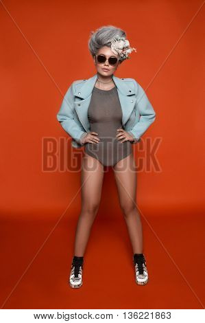 Girl with grey hair and flower in body and jacket standing in studio, color orange background, nude makeup with natural browes and pink lips, sunglasses on face