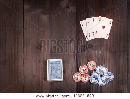 Chips and Four aces vintage poker game playing cards on a weathered wood table view from above.