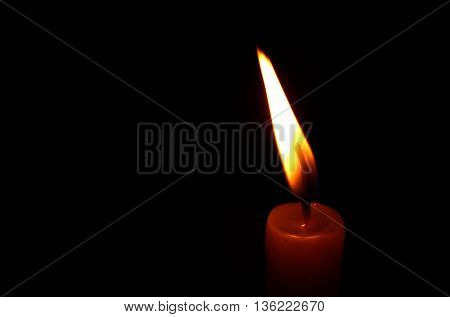 One candle flame at night closeup - isolated