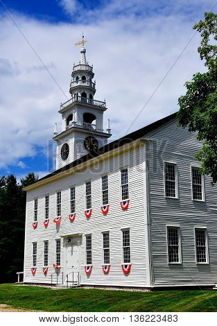 Jaffrey Center New Hampshire - July 11 2013: Red white and blue bunting hangs from the windows of the 1775 Original Meeting House church with its elegant steeple and bell tower