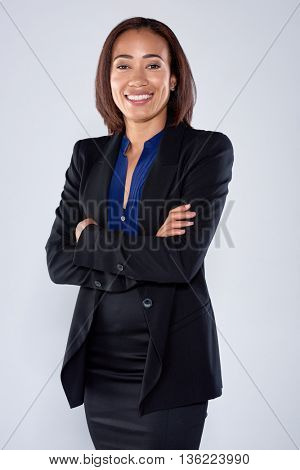 Confident business woman portrait wearing a black suit, smiling with arms crossed