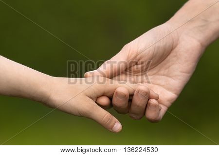 Mother holding a hand of her daughter on blurred background closeup