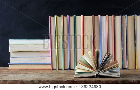 Books in the colored covers on the shelf in the background of a school blackboard. Open book.