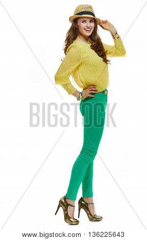 Colourful shopping vibes. Full length portrait of smiling brunette woman in hat and bright clothes looking aside on white background