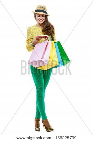Smiling Woman With Shopping Bags Writing Sms On White Background