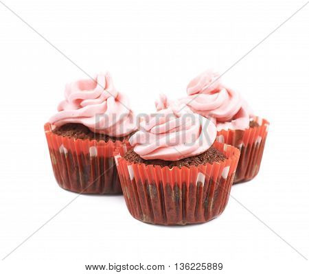 Three chocolate muffins coated with the pink cream frosting, composition isolated over the white background