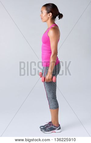 Side profile of hispanic latino woman working out with dumbbells happy and healthy lifestyle