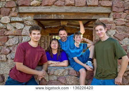 A family of five with three boys poses for a portrait in front of a rock structure.