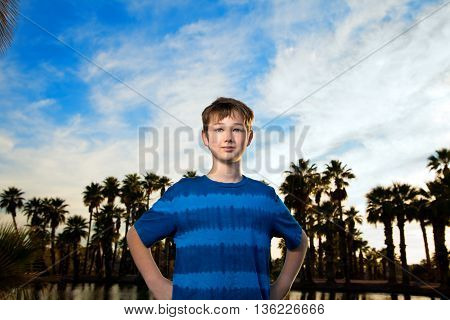A tween boy stands in a super hero stance against a blue cloudy sky and palm trees by a lake.