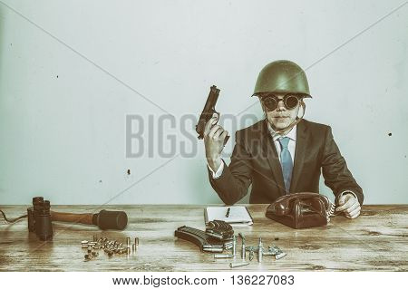 Vintage military businessman sitting at office desk with hand gun and military stuff
