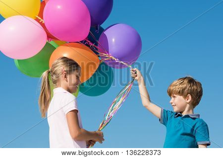 Young boy taking balloons from friend. Sister sharing colorful balloons with brother. Children playing with colorful balloons.