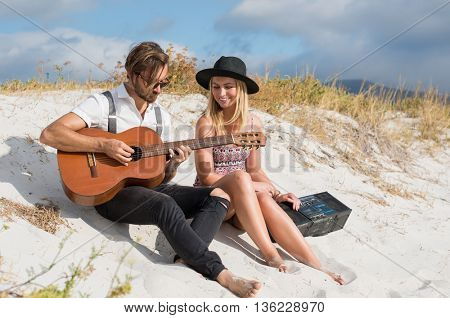 Happy couple playing guitar on beach. Loving young couple sitting on beach. Smiling girl and guy with guitar and radio having fun on beach.