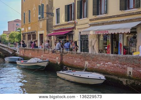 Venice, Italy, June, 21, 2016: people in a cafe near a channel in Venice, Italy
