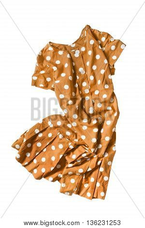 Yellow dress with polka dots folded on white background
